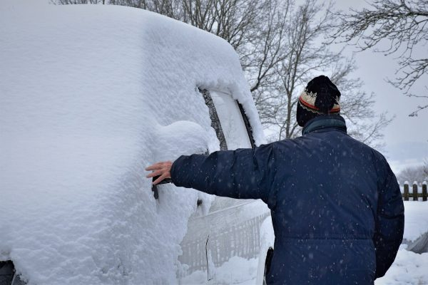 Man touches his snow covered vehicle