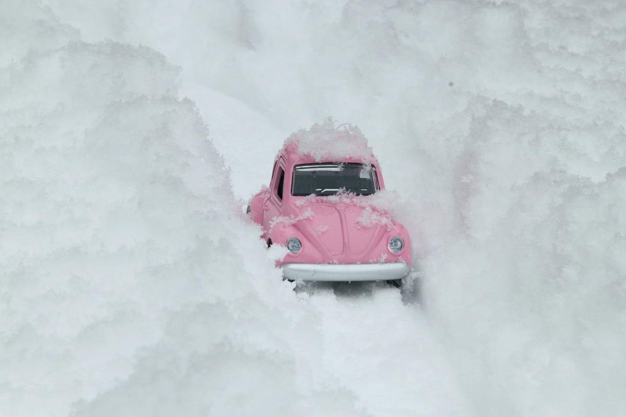 Pink car driving between walls of snow