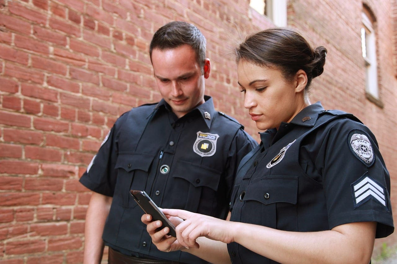 Police officers doing research on a smartphone