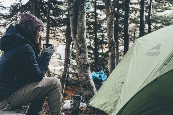 Woman enjoying a cup of coffee at her campsite after a stressful week