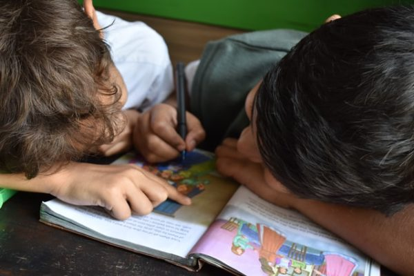 Two children writing in a workbook.