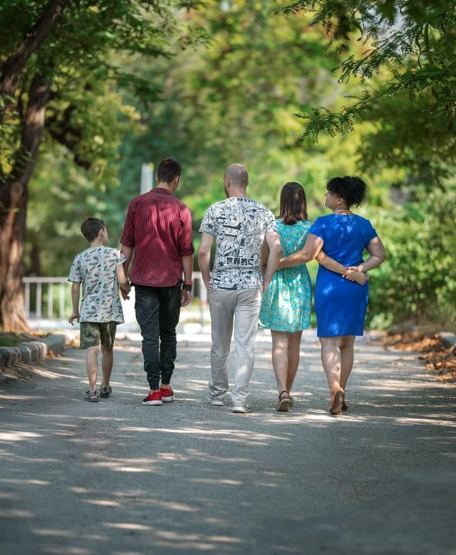 A family facing away from the camera and walking down the road.