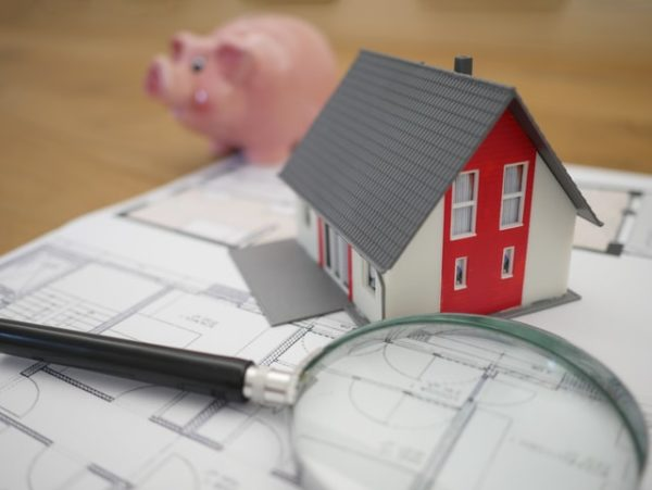 House plans, a magnifying glass, a small house model, and a piggy bank are laid out on a table.